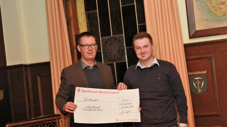 Andreas Augstein übergibt einen Scheck an den Schulverband der Gemeinschaftsschule St. Michaelisdonn